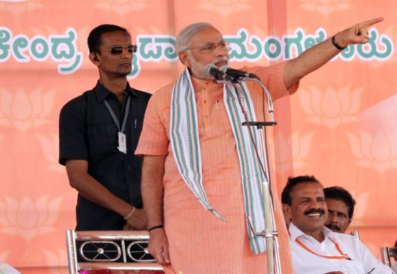 Narendra Modi gestures while addressing supporters at a campaign rally in Mangalore on Thursday