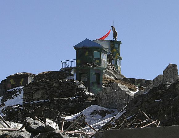 Chinese soldiers put up a flag atop their border post