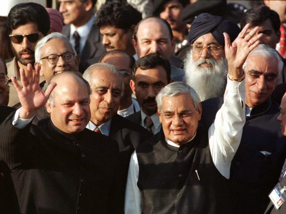 Former Pakistan prime ministers Nawaz Sharif (L) and his Indian counterpart Atal Behari Vajpayee (R) wave to a crowd at Wagah border near Lahore
