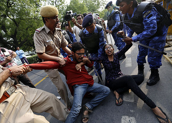 Police try to stop protestors during a demonstration against sexual violence in Delhi