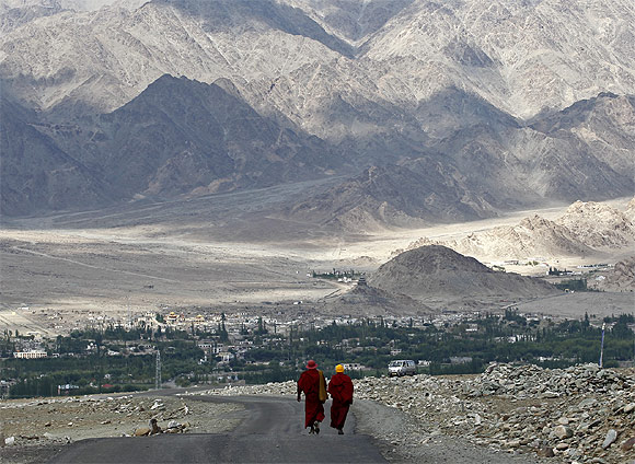 Buddhist monks walk on a road in Stok, 20 km north of Leh