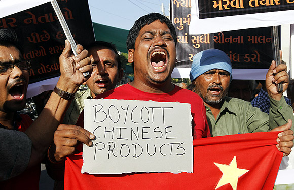 Traders shout slogans during a protest against China
