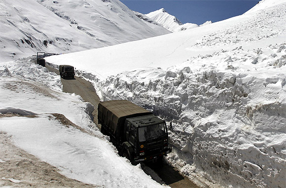 Indian Army vehicles move between walls of snow on the Srinagar-Leh highway