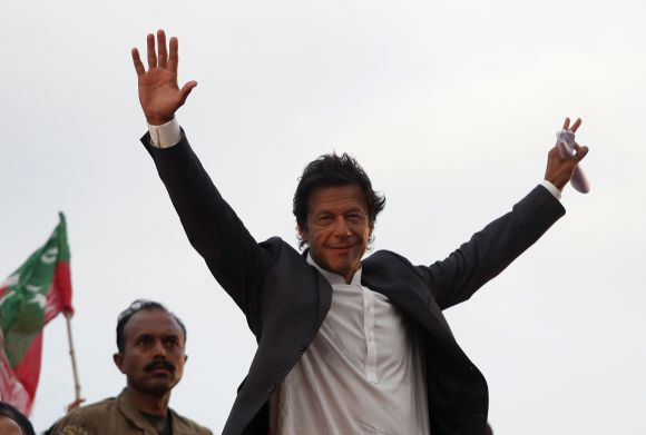 Imran Khan, Pakistani cricketer-turned-politician, Chairman of political party Pakistan Tehreek-e- Insaf (PTI) waves to his supporters during a rally in Lahore