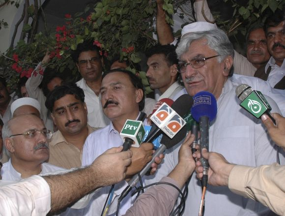 Asfandyar Wali Khan (R), leader of the Awami National Party (ANP), speaks to the media