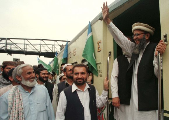 Sayed Munawar Hassan, acting chief of the religious Jama'at-i-Islami (JI) party, waves to supporters at Rawalpindi railway station