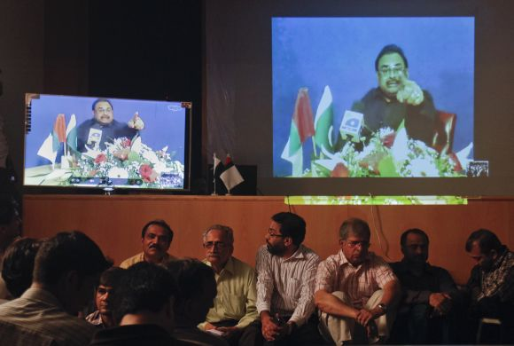 Supporters of Muttahida Qaumi Movement surround television screens broadcasting a speech by their party leader Altaf Hussain from London via video conference in Karachi