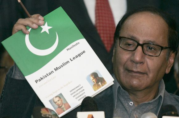 Pakistan Muslim League President Chaudhry Shujaat Hussain shows the media his party manifesto during a news conference in Islamabad