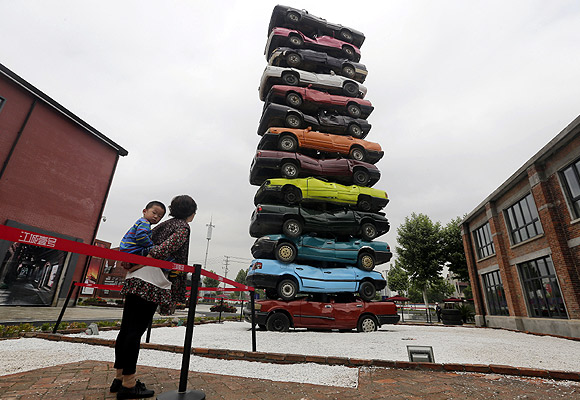 People look at a sculpture made of 13 scrapped cars of various colours at a cultural industrial park in Wuhan, Hubei province