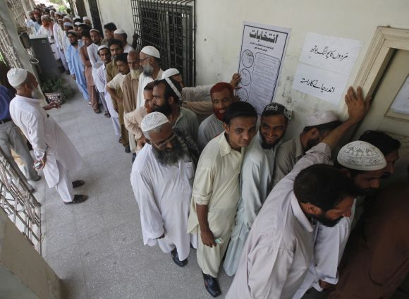 Voters line up as they wait for their turn to cast their vote at a polling station in Karachi on Saturday.