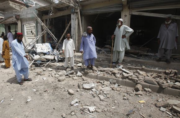 Residents gather at the site of a bomb attack near a polling station in Karachi on Saturday