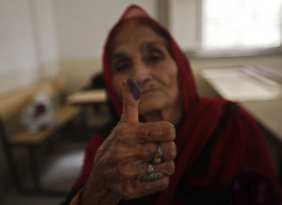 A woman voter displays her inked thumb at a polling station in Karachi