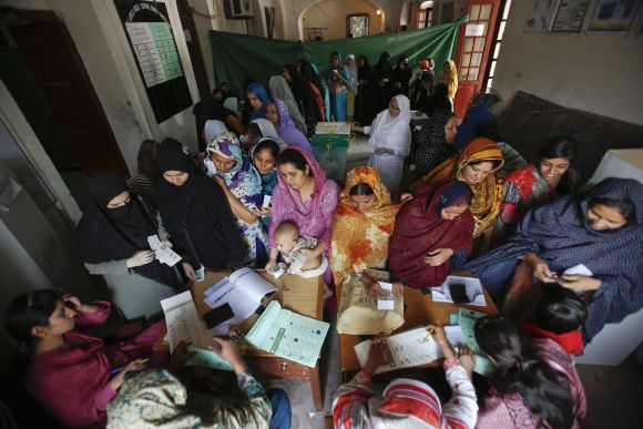 Women register and cast their ballots at a polling station in the old part of Lahore Saturday.