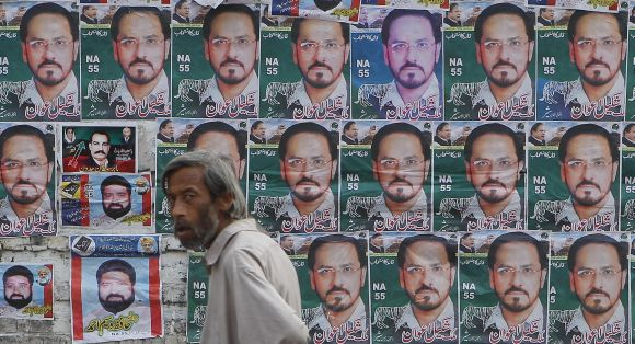A man walks past election posters of Malik Shakeel Awan, a candidate of the Pakistan Muslim League, outside a polling station in Rawalpindi Saturday.