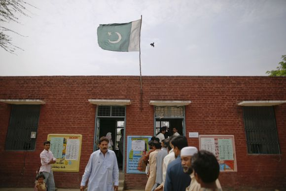 A flag and a bird fly over a polling station as people wait to cast their votes in a village near Lahore on Saturday.