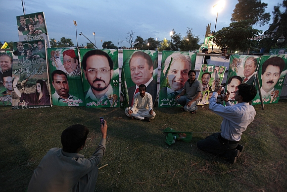 Supporters of the PML-N party take pictures in front of banners of Nawaz Sharif (centre) and other party leaders during an election campaign rally in Rawalpindi