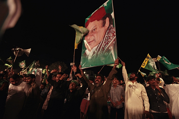 Supporters of the PML-N hold the portrait of party leader Nawaz Sharif as they shout slogans during an election campaign rally in Rawalpindi.