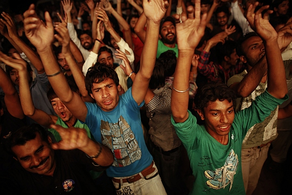Supporters of the PML-N celebrate in front of a party office as results of the general election come in, in Lahore