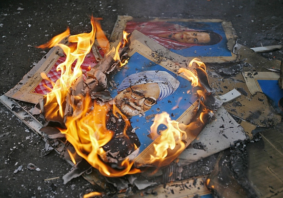 Portraits of Prime Minister Manmohan Singh and  Congress president Sonia Gandhi lie in flames after they were set alit by the demonstrators during a protest in Ahmedabad