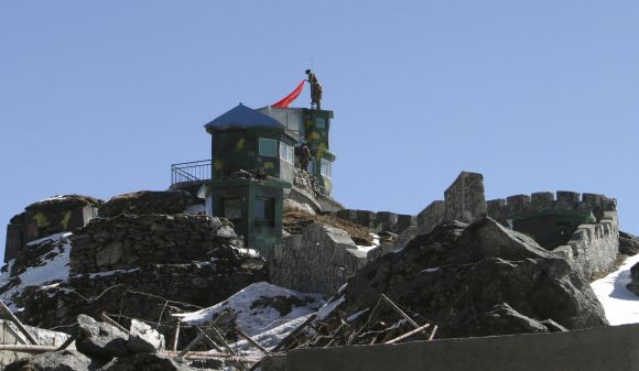 A Chinese soldier put up a flag atop their post at the Indo-China border in Nathula Pass in Sikkim