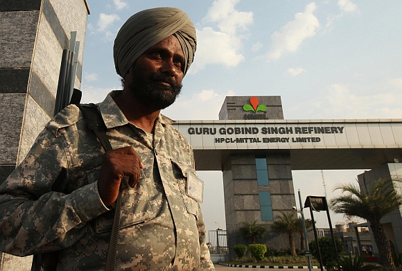 A security personnel stands guard in front of the main entrance of the Guru Gobind Singh oil refinery near Bhatinda in Punjab