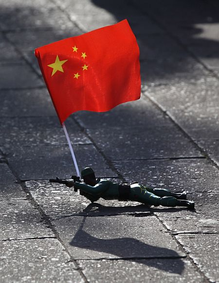 A electric toy soldier crawls on the ground outside the Forbidden City in Beijing, China
