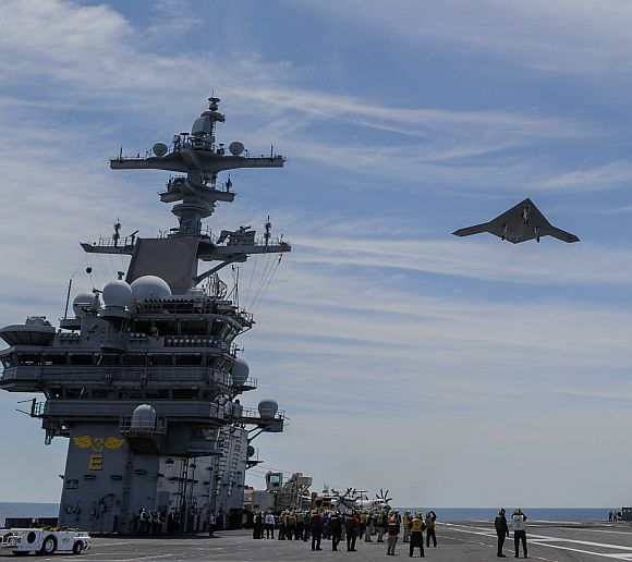 An X-47B Unmanned Combat Air System demonstrator flies over the aircraft carrier USS George HW Bush