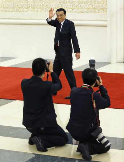 China's Premier Li Keqiang waves as he leaves after the annual news conference at the Great Hall of the People in Beijing