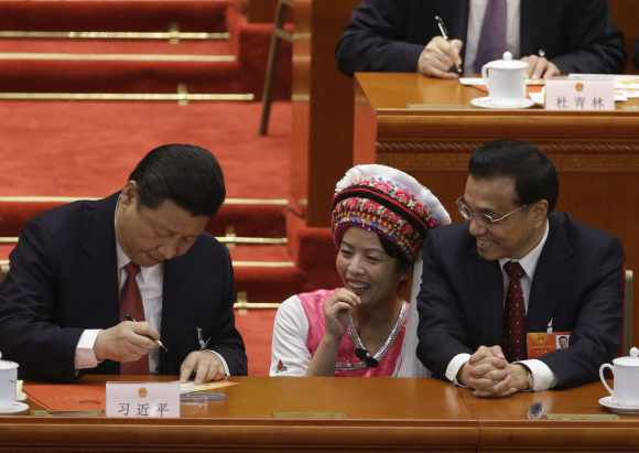 Li Keqiang and an ethnic minority delegate look at China's President Xi Jinping signing an autograph at the Great Hall of the People in Beijing