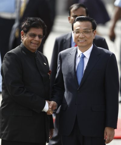 Li Keqiang shakes hands with Minister of State for External Affairs E Ahmed upon his arrival at the airport in New Delhi.
