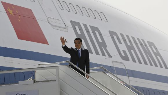 Chinese Premier Li Keqiang waves upon his arrival at the airport in New Delhi