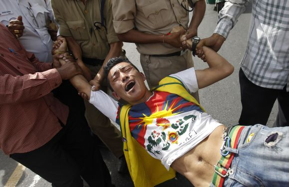 A Tibetan exile is detained by police outside the Chinese embassy during a protest against the visit of Li Keqiang, in New Delhi, on Sunday