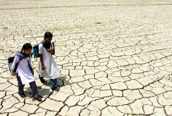 Two Indian students walk through a dry paddy field in Raipur village in Punjab