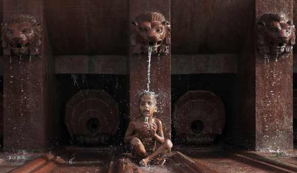 A boy cools himself off as he sits under a fountain on a hot summer day in New Delhi