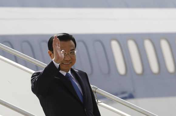 Li Keqiang waves upon his arrival at the airport in New Delhi