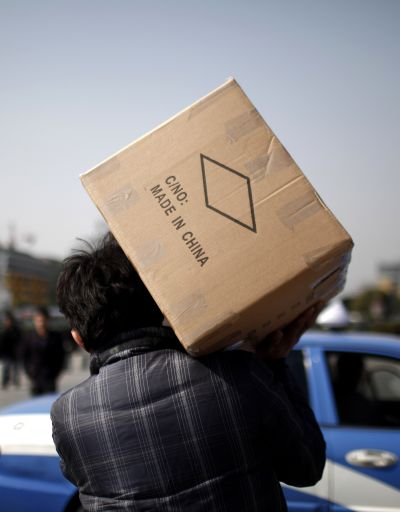 A man carries a box with products made in China at a wholesale market in Yiwu, Zhejiang province.