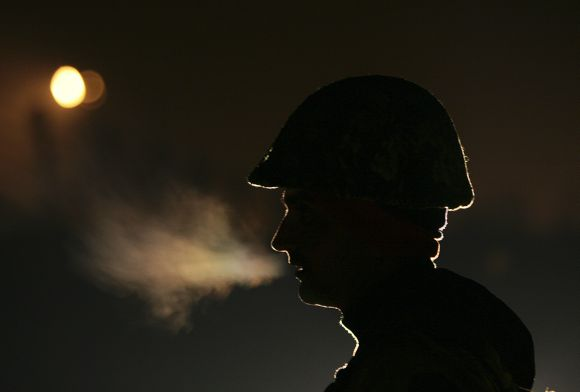 A BSF soldier keeps vigil during night patrol near a fenced border in Jammu and Kashmir