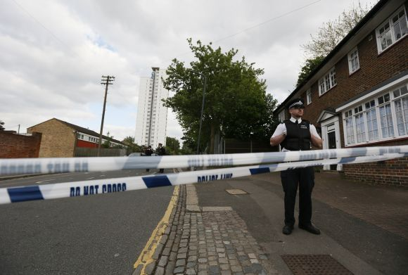 Police officers guard a cordon set up around a crime scene where one man was killed in Woolwich