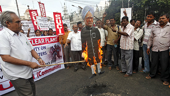 Activists burn a picture of Prime Minister Manmohan Singh during a protest against alleged police torture on demonstrators near the Kudankulam nuclear power project
