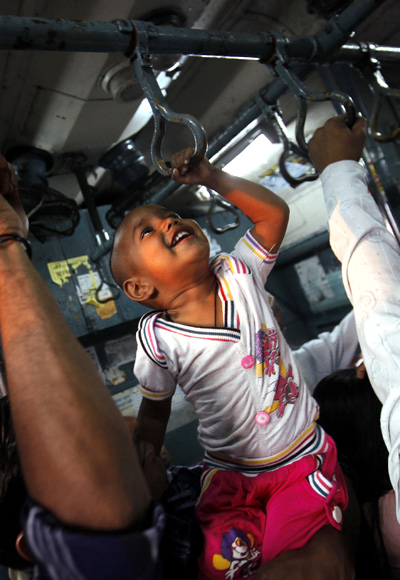 A child tries to hold onto the handrails in a crowded suburban train during rush hour in Mumbai