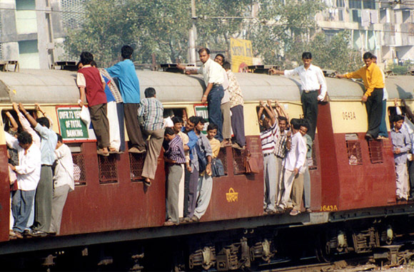 Office-goers travel atop a crowded suburban train