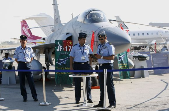 Pakistani pilots stand in front of the JF-17 Thunder fighter plane during the Dubai Airshow