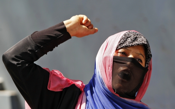 A veiled Kashmiri Muslim woman shouts slogans during a protest rally in Srinagar