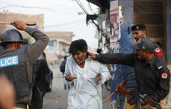Police beat and detain a Pakistani Christian protester during a demonstration in Badami Bagh, Lahore