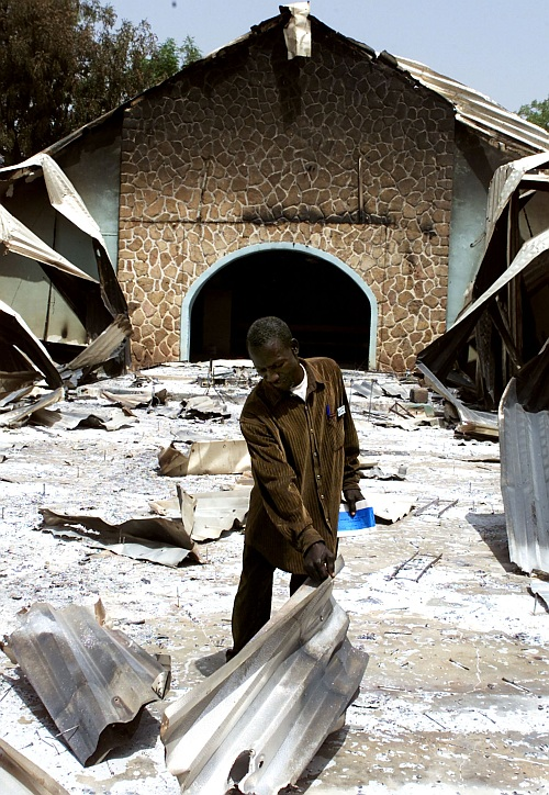 Nigerian James Alkali searches through the burnt remains of the Church of Christ, February 27, 2004, in which 48 Christians were massacred in Yelwa, Plateau state in central Nigeria