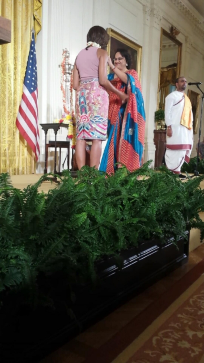 Mythili Bachi chairperson the Sri Siva Vishnu Temple garlands Michelle Obama at the Diwali celebrations