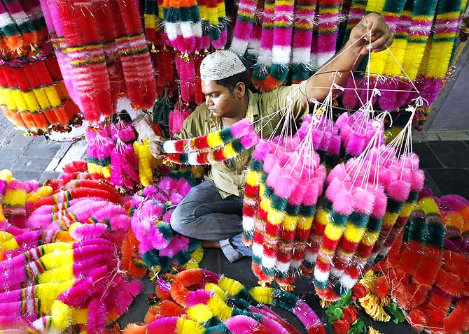 A vendor arranges garlands for sale in his shop before the festival of lights, Diwali in Ahmedabad, Gujarat.