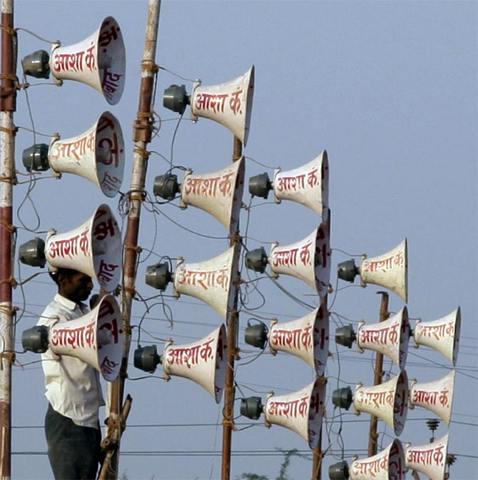 A worker installs loudspeakers at the venue of a campaign rally on the outskirts of Allahabad, 2011.