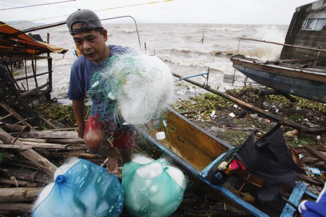 A fisherman carries his net after making it safely back to shore after a strong winds from Typhoon Haiyan battered Bayog town in Los Banos, Laguna city, south of Manila, on Friday.