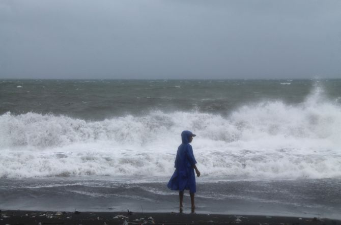 A resident walks along a shoreline as strong winds brought by super Typhoon Haiyan battered San Roque town, Legazpi city, south of Manila